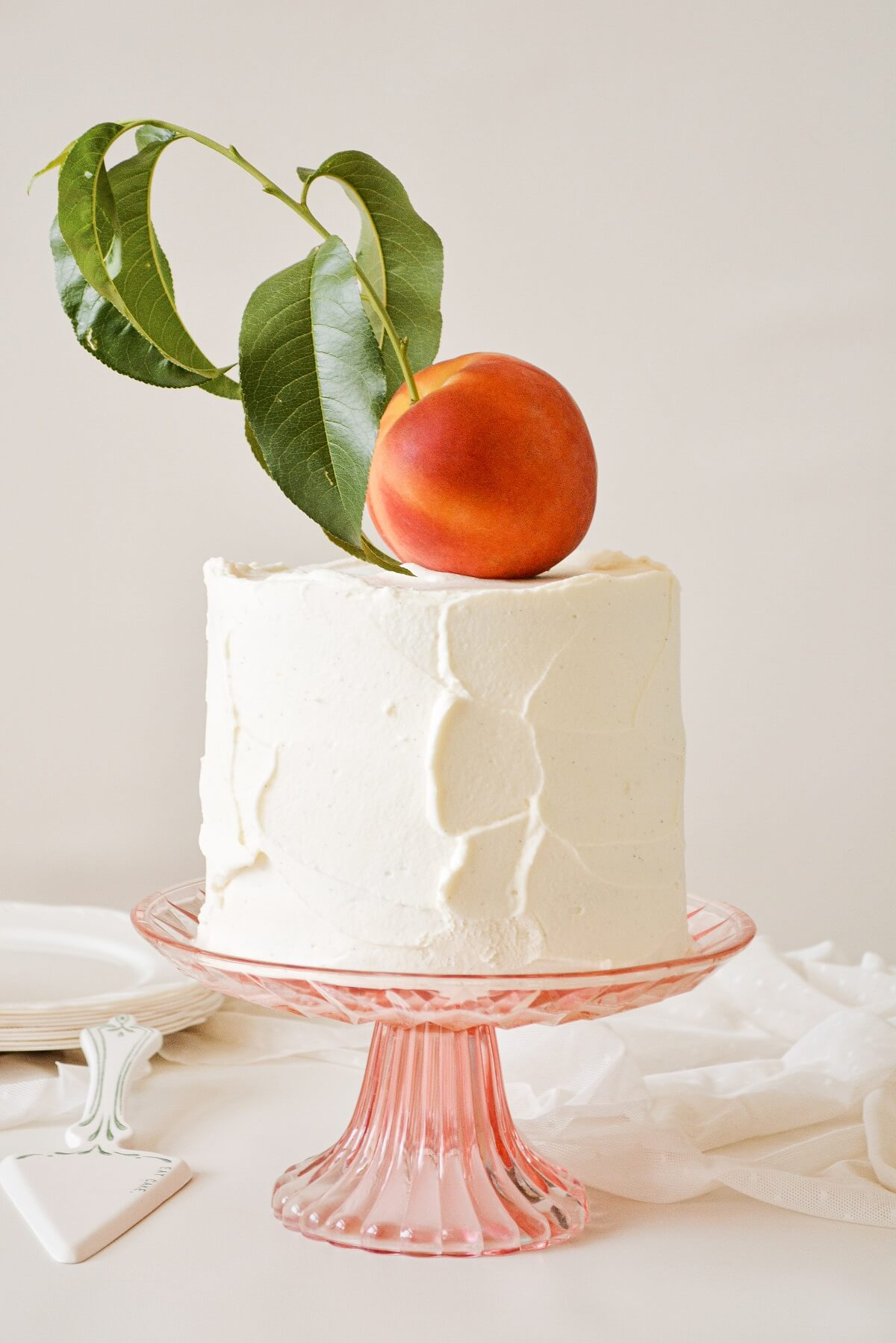 Peaches and cream cake, topped with a whole peach.