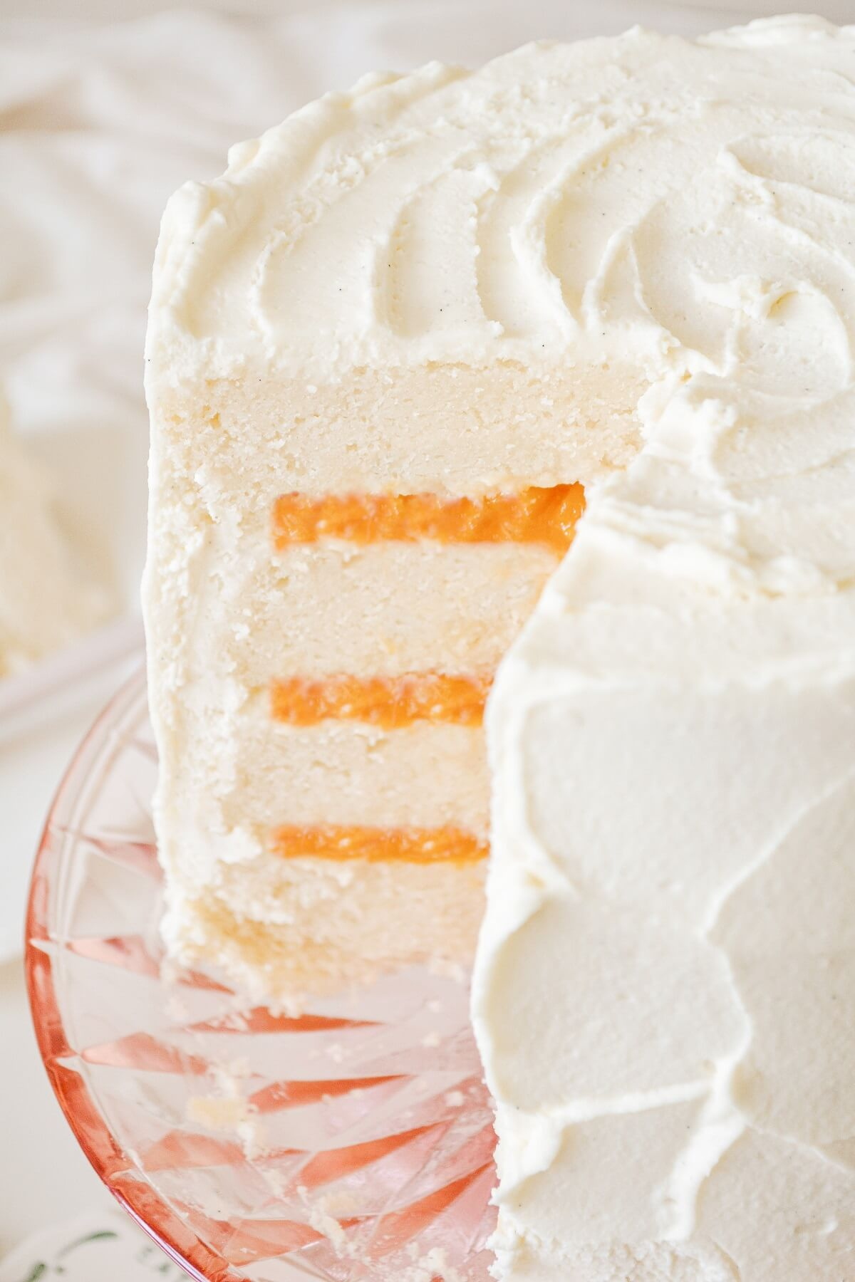 Peaches and cream cake, with one slice cut.