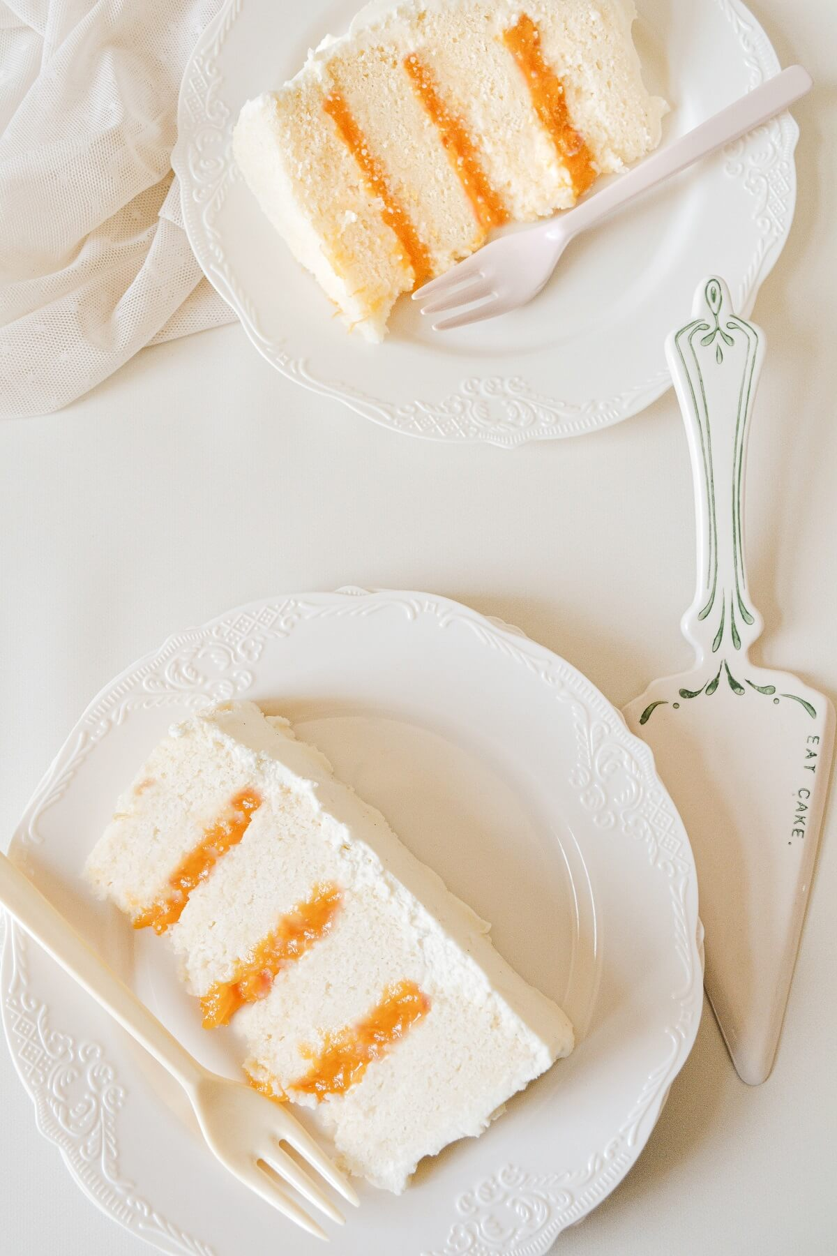 Slices of peaches and cream cake on white plates.