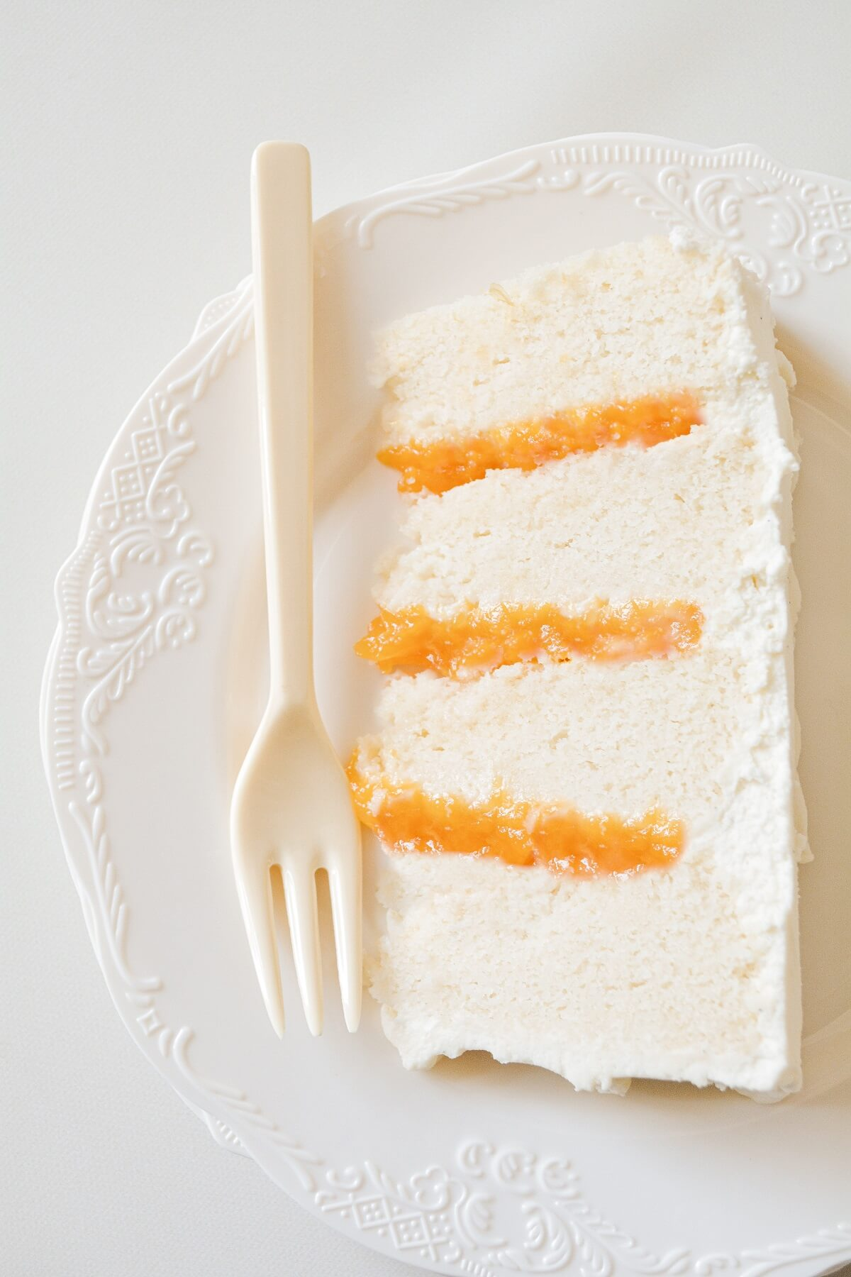 A slice of peaches and cream cake on a white plate.