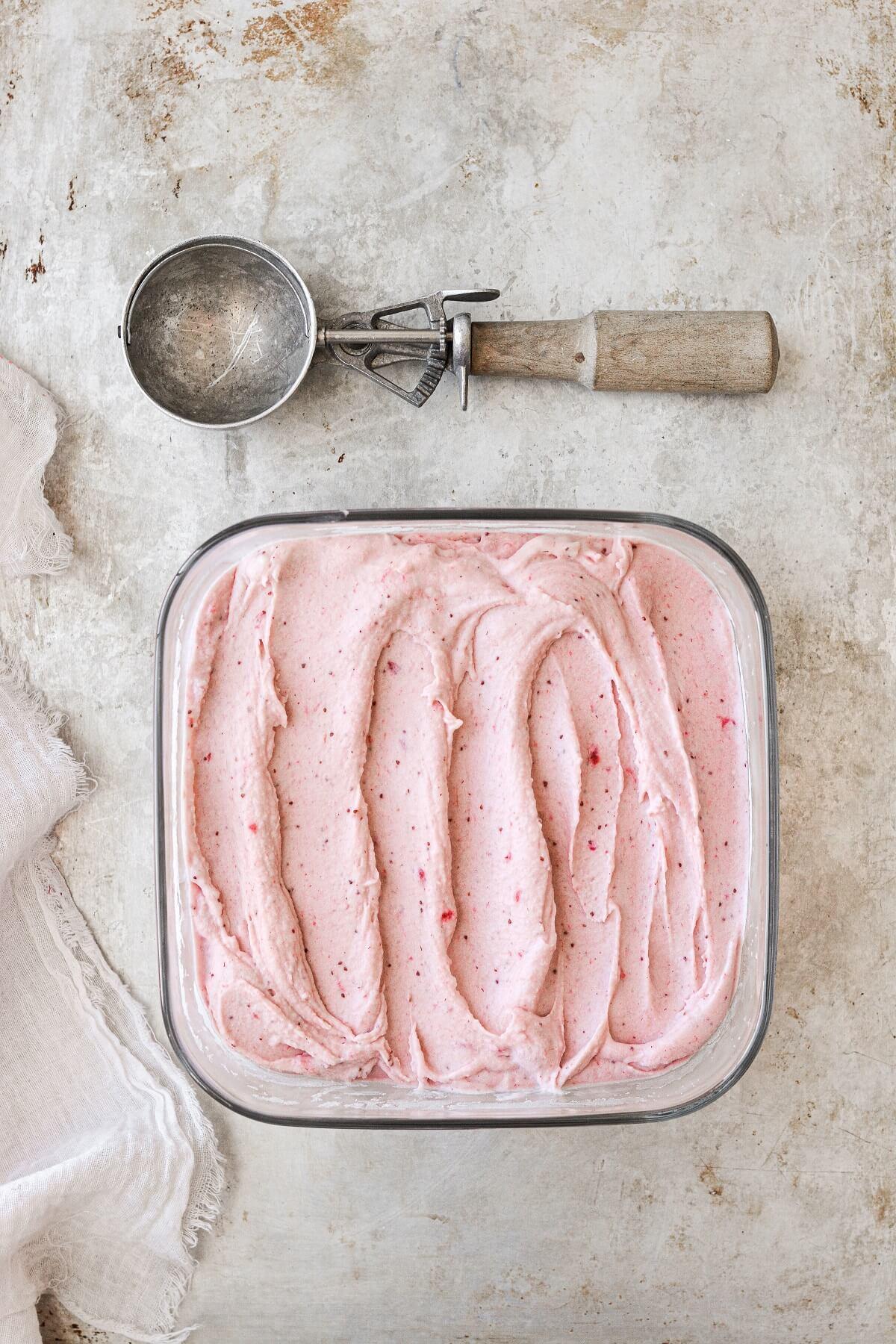 Roasted strawberry ice cream, next to a vintage ice cream scoop.