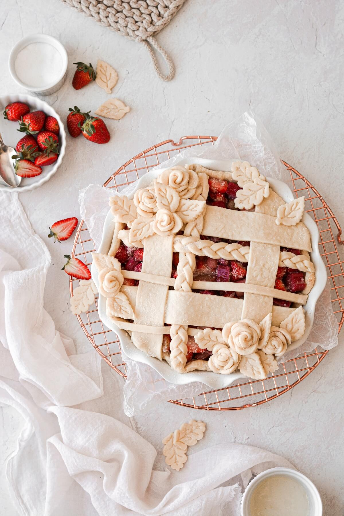 An unbaked strawberry rhubarb pie, with a lattice top and pie dough roses.