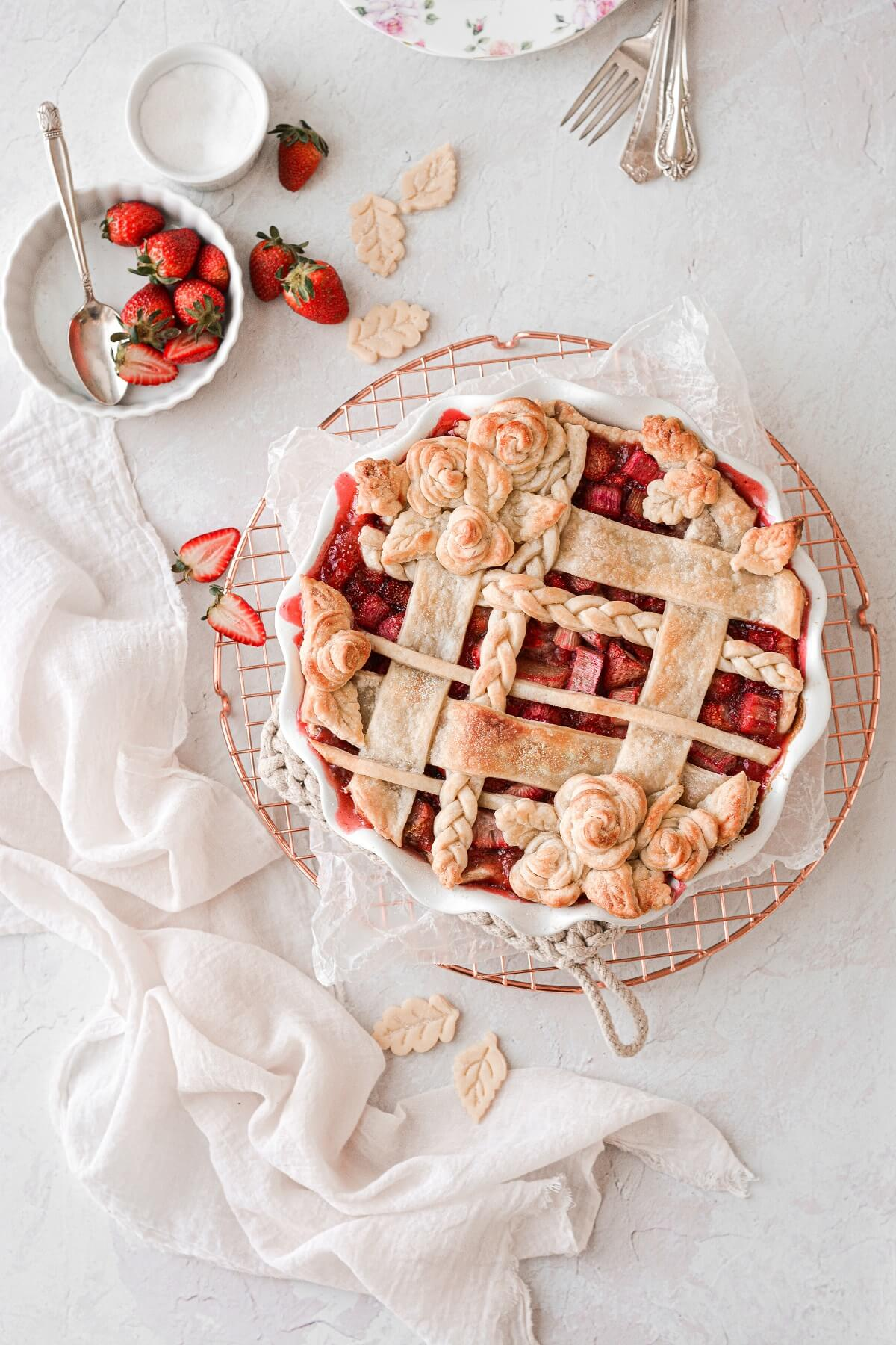 Strawberry rhubarb pie, with a lattice top and pie dough roses.