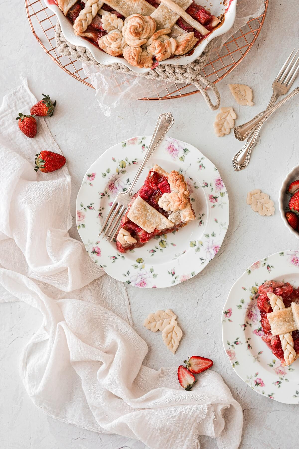 Slices of strawberry rhubarb pie, on flowered plates.