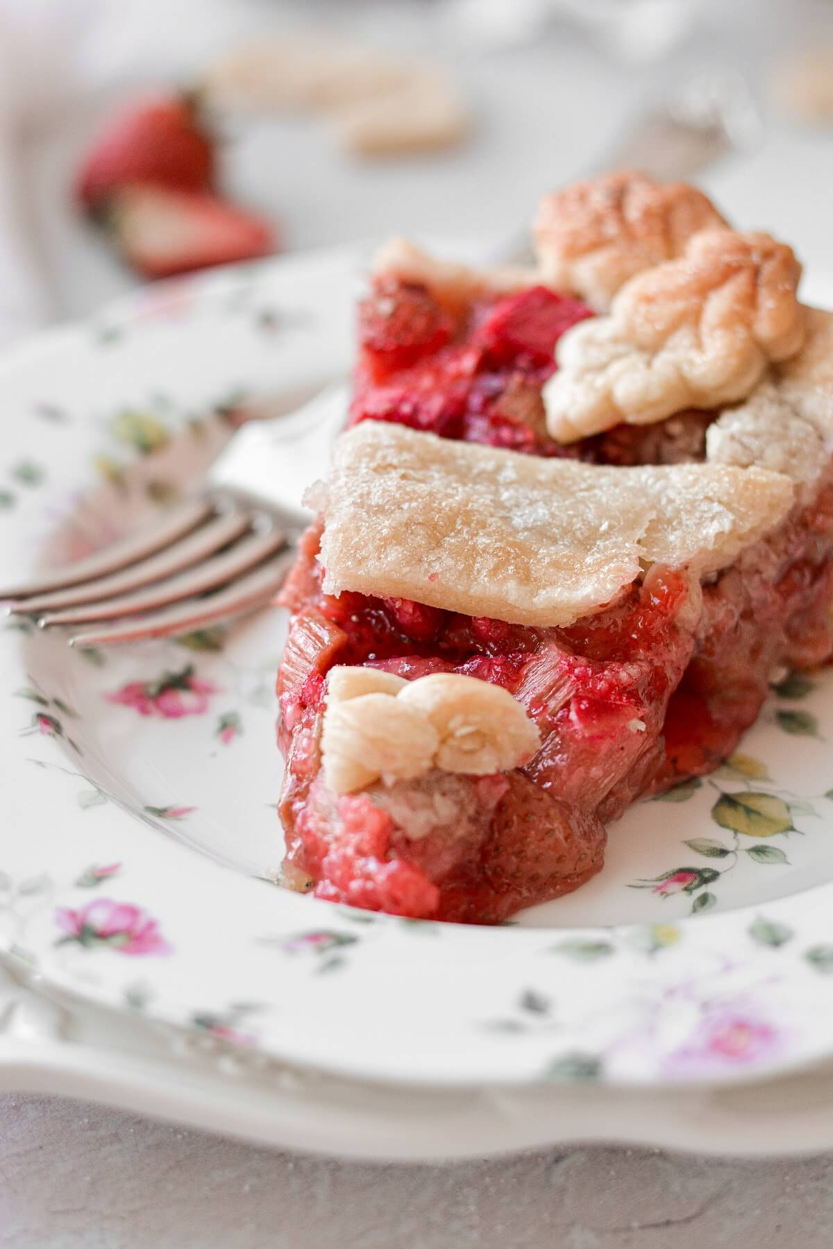 A slice of strawberry rhubarb pie, on a flowered plate.
