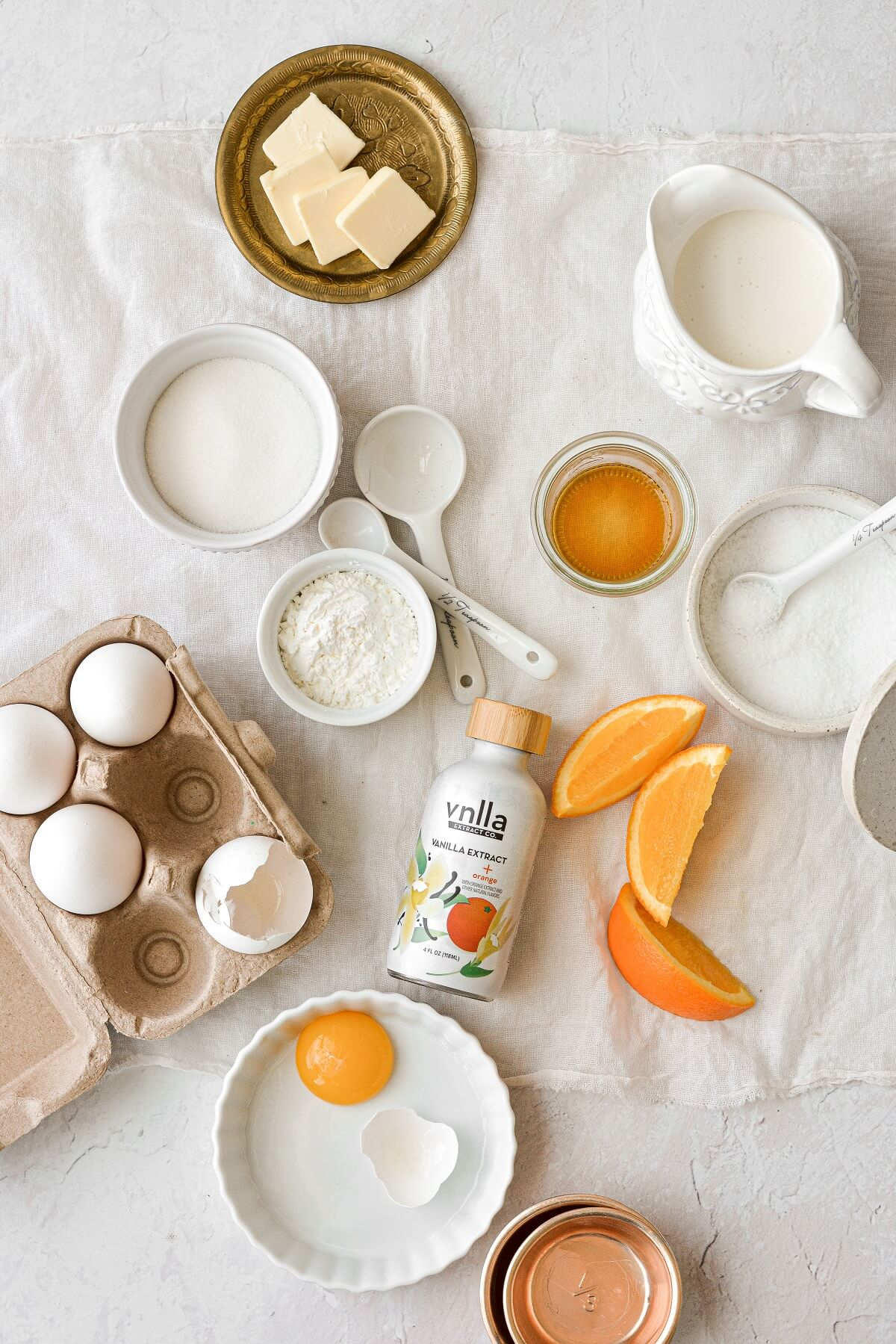Ingredients for orange vanilla custard spread out on a white linen.