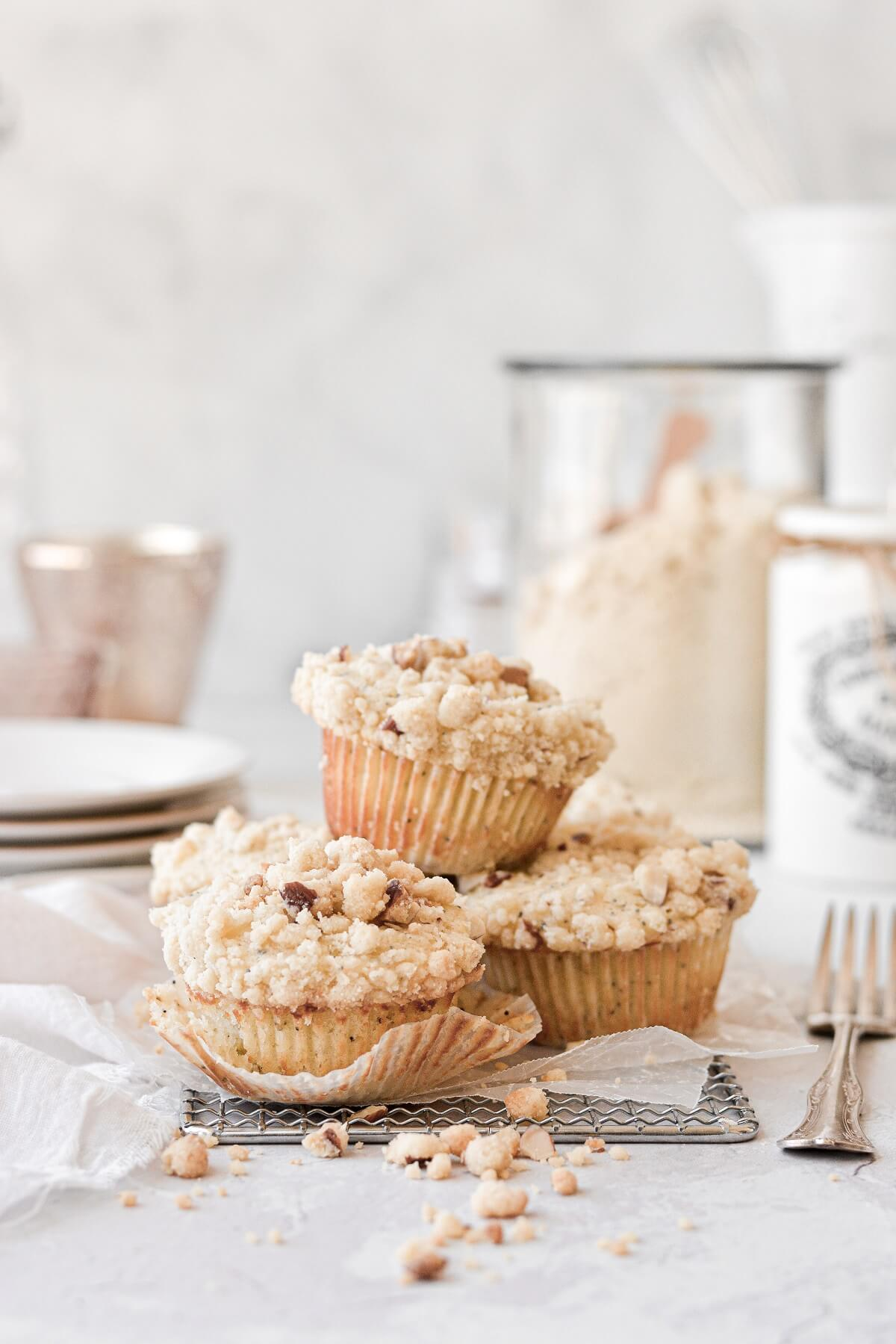 Almond poppy seed muffins, piled on top of a cooling rack.