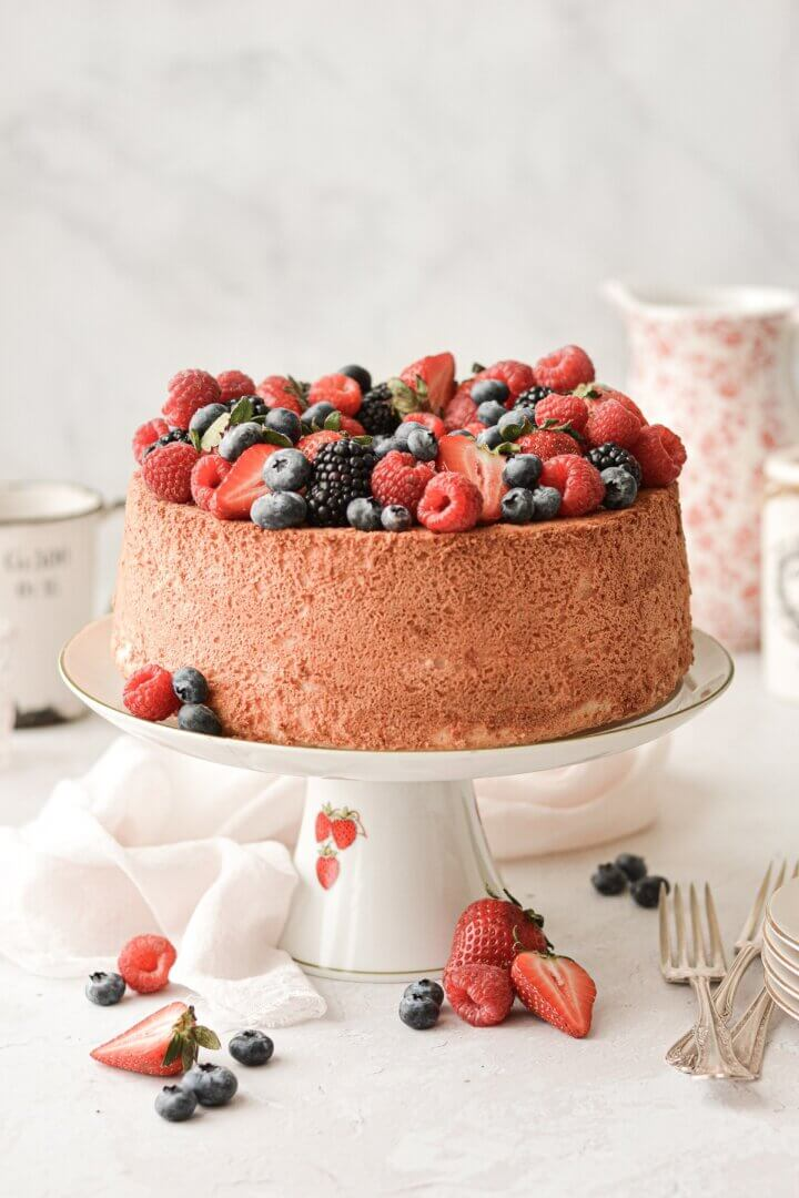 Angel food cake on a vintage cake stand, topped with assorted berries.