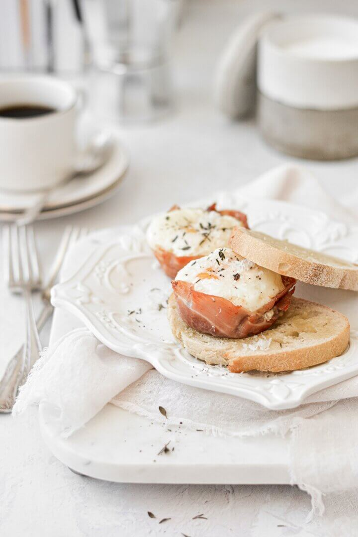 Baked prosciutto egg cups, sprinkled with thyme and parmesan, served with toast.