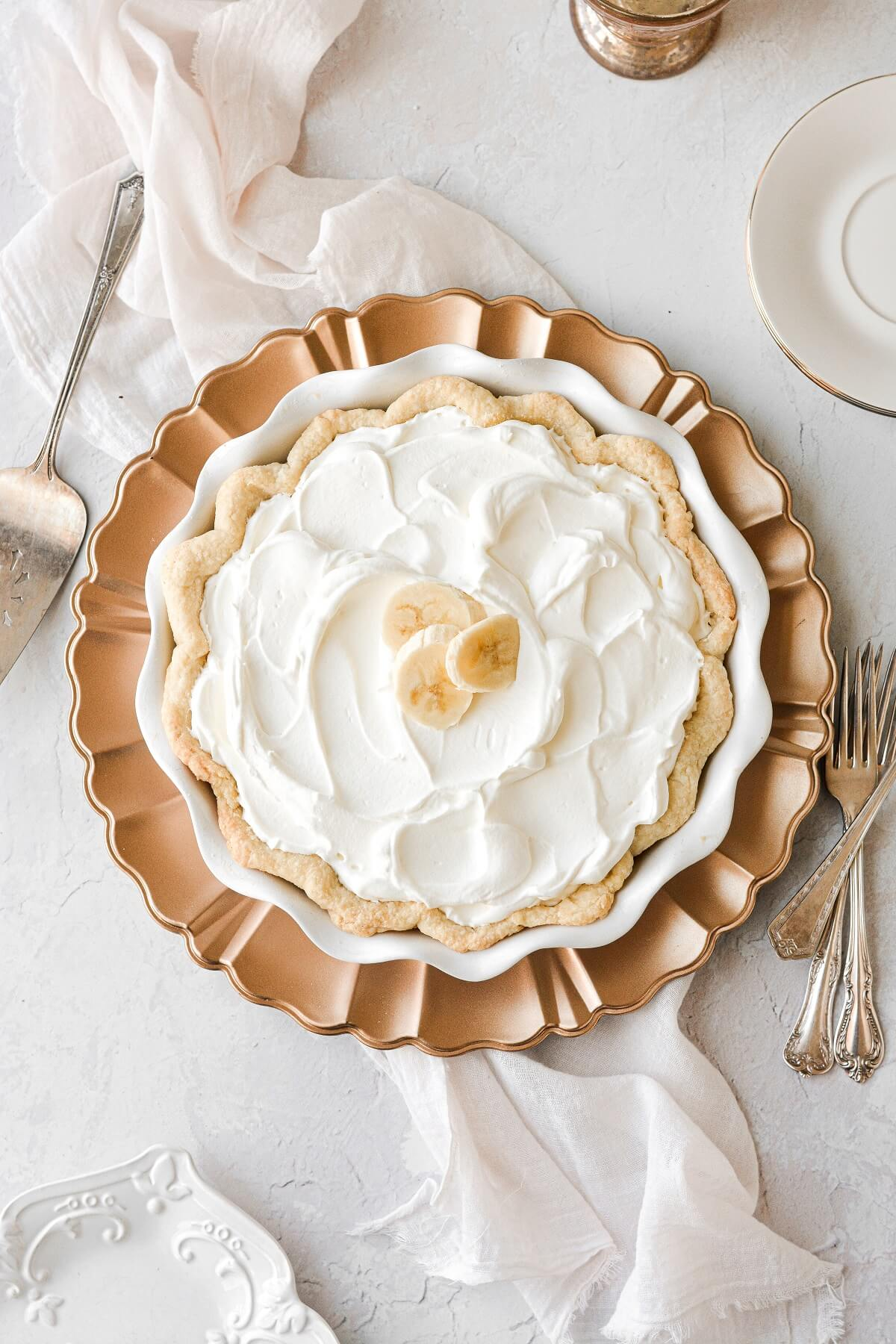 Banana cream pie, topped with whipped cream and sliced bananas.