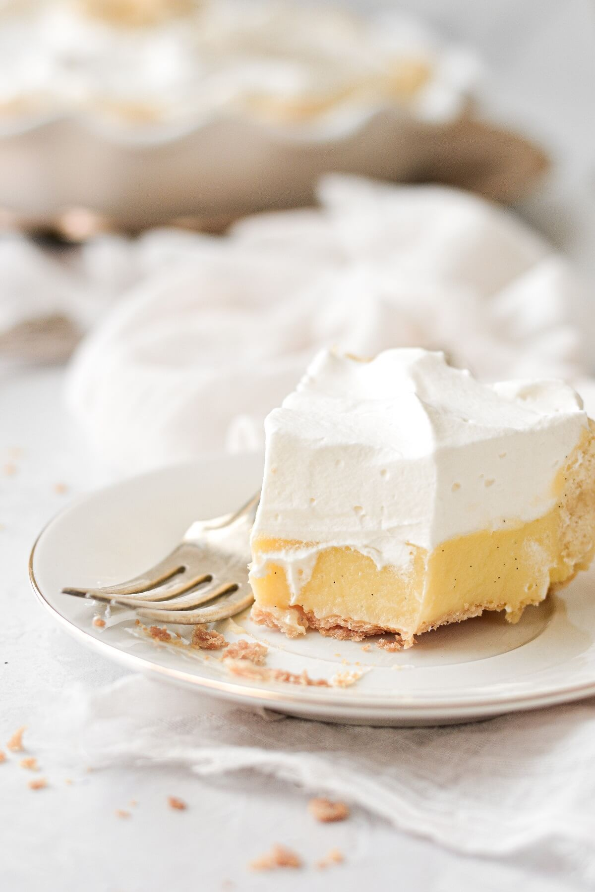 A slice of banana cream pie with one bite taken.