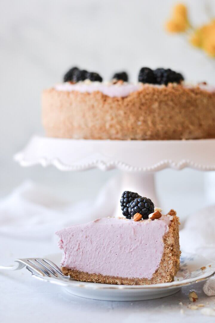 A slice of no bake blackberry cheesecake, topped with blackberries.