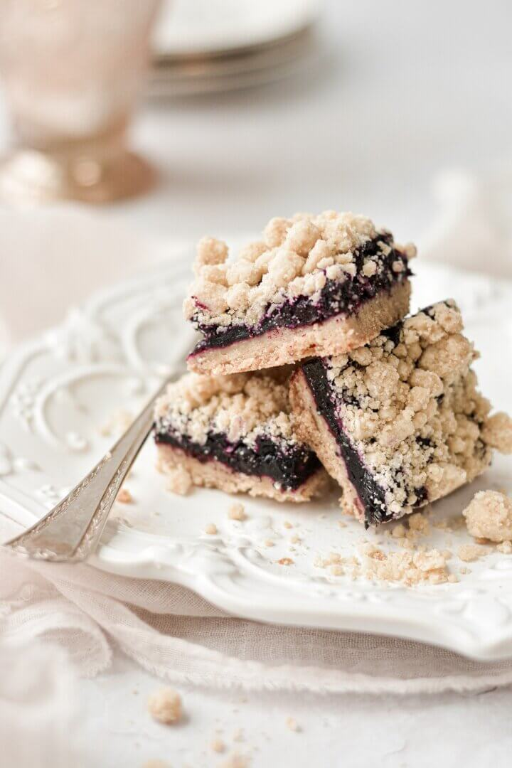 Blueberry crumb bars arranged on a plate.