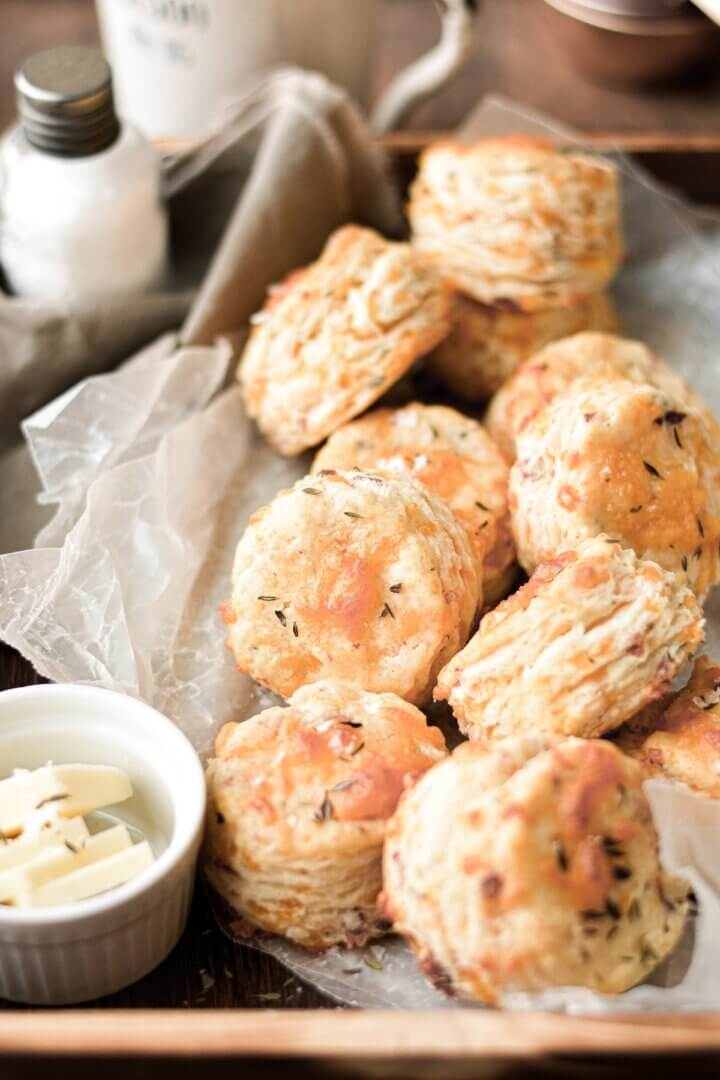 Cheesy herb biscuits arranged on a wooden tray with butter and salt.