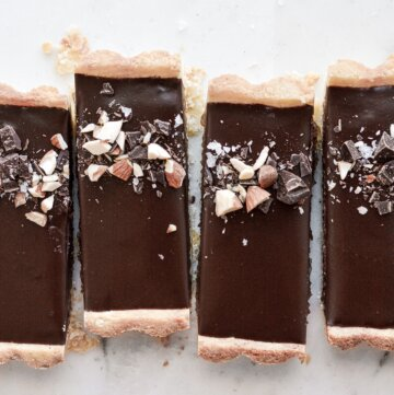 Slices of chocolate almond tart, sprinkled with chopped chocolate and almonds.