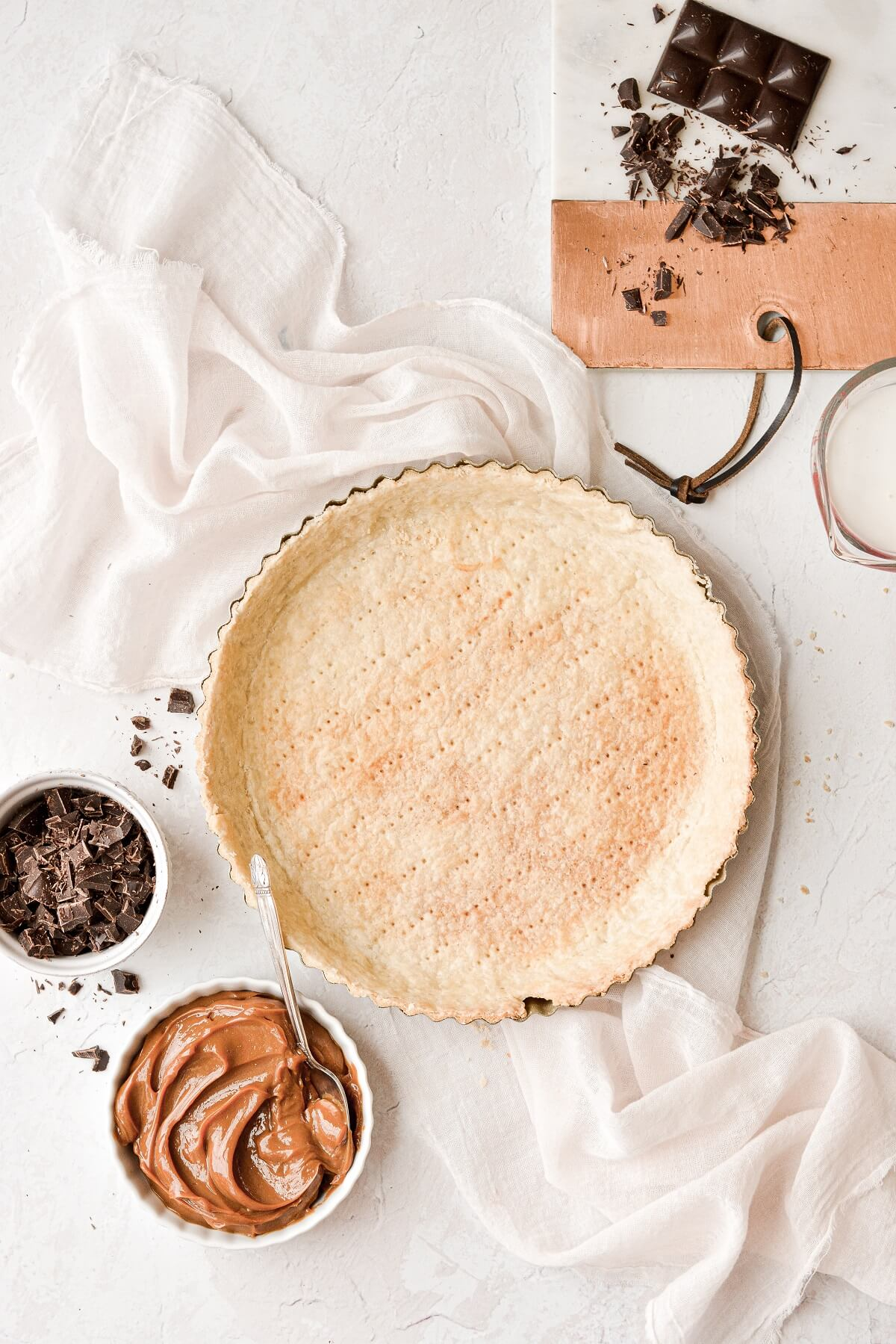 A baked tart shell, ready to be filled with caramel and chocolate ganache.