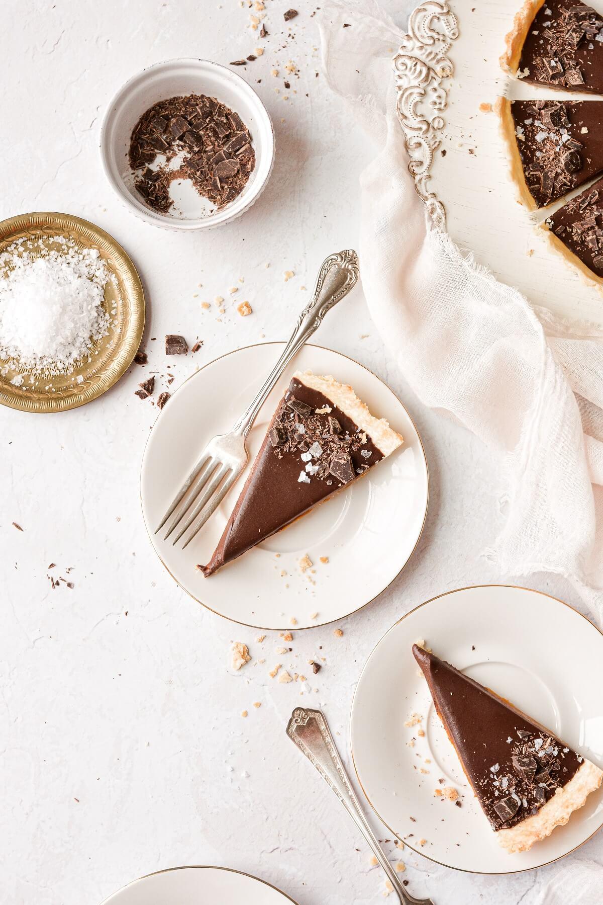 Slices of chocolate caramel tart on white plates.