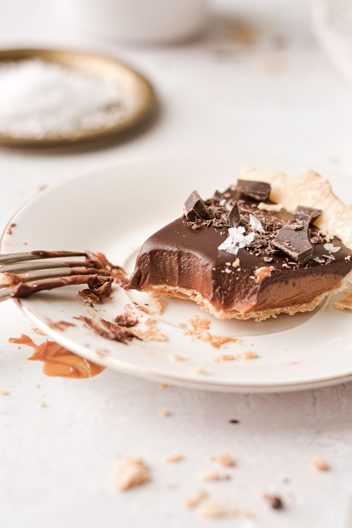 A slice of chocolate caramel tart with a bite taken.