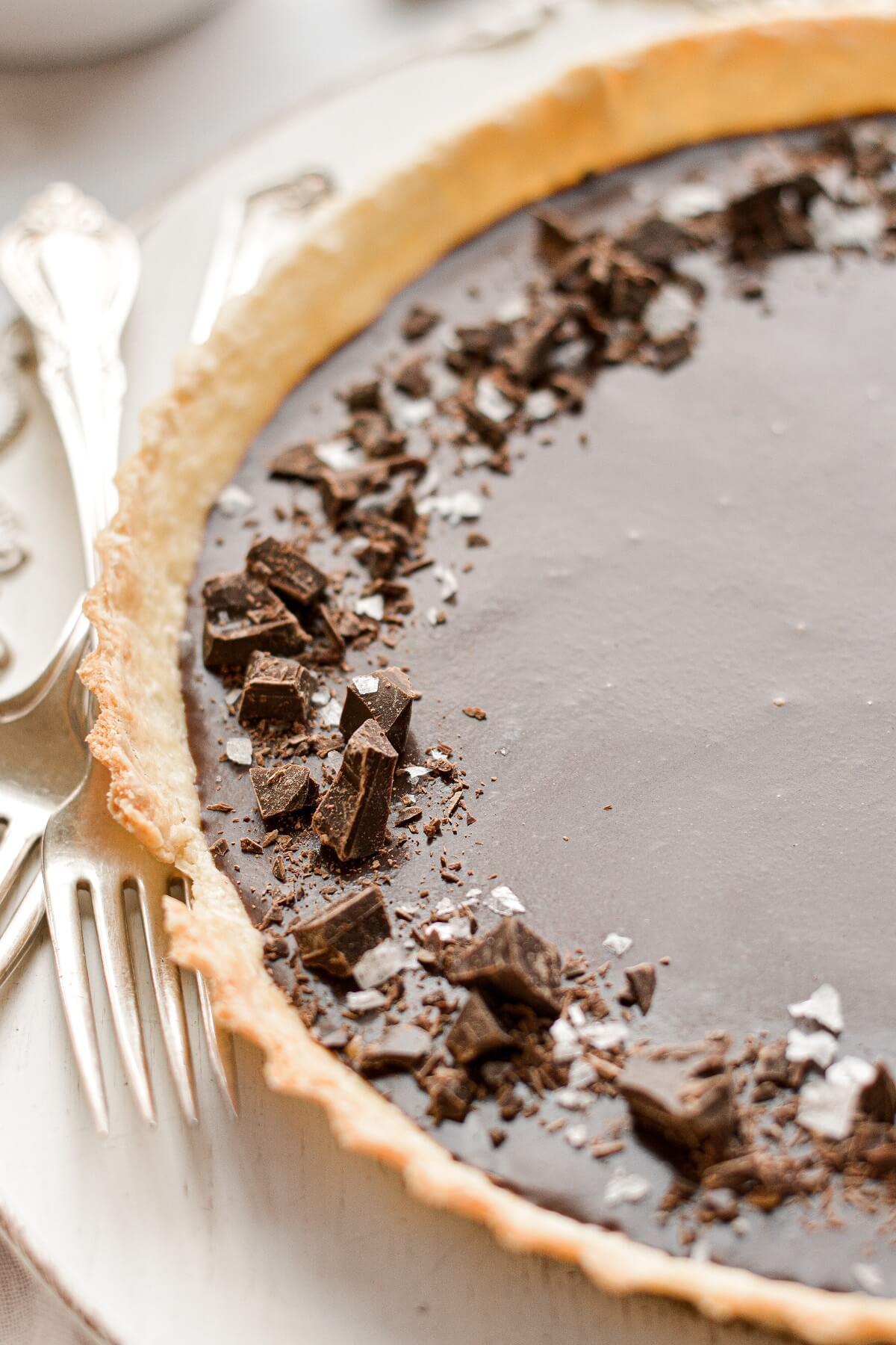 A chocolate caramel tart, sprinkled with chopped chocolate and flaky sea salt.