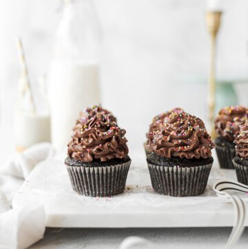 Chocolate cupcakes with chocolate buttercream, sprinkled with rainbow sprinkles.