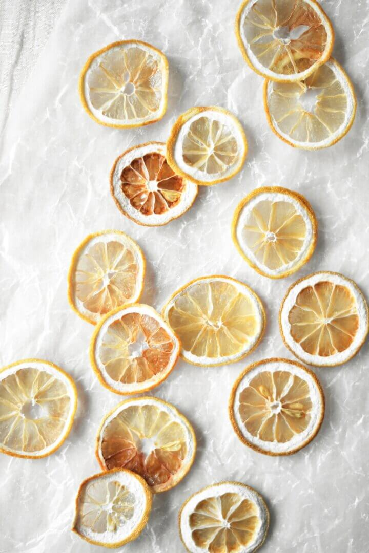 Dried lemon slices on crumpled wax paper.