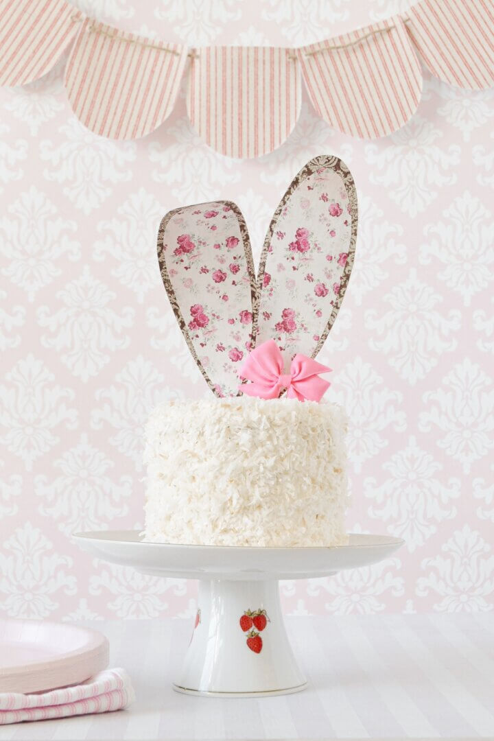 An Easter bunny coconut cake with paper floral ears, and a pink candy bow.