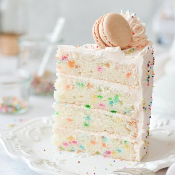 A slice of funfetti cake, topped with a macaron.