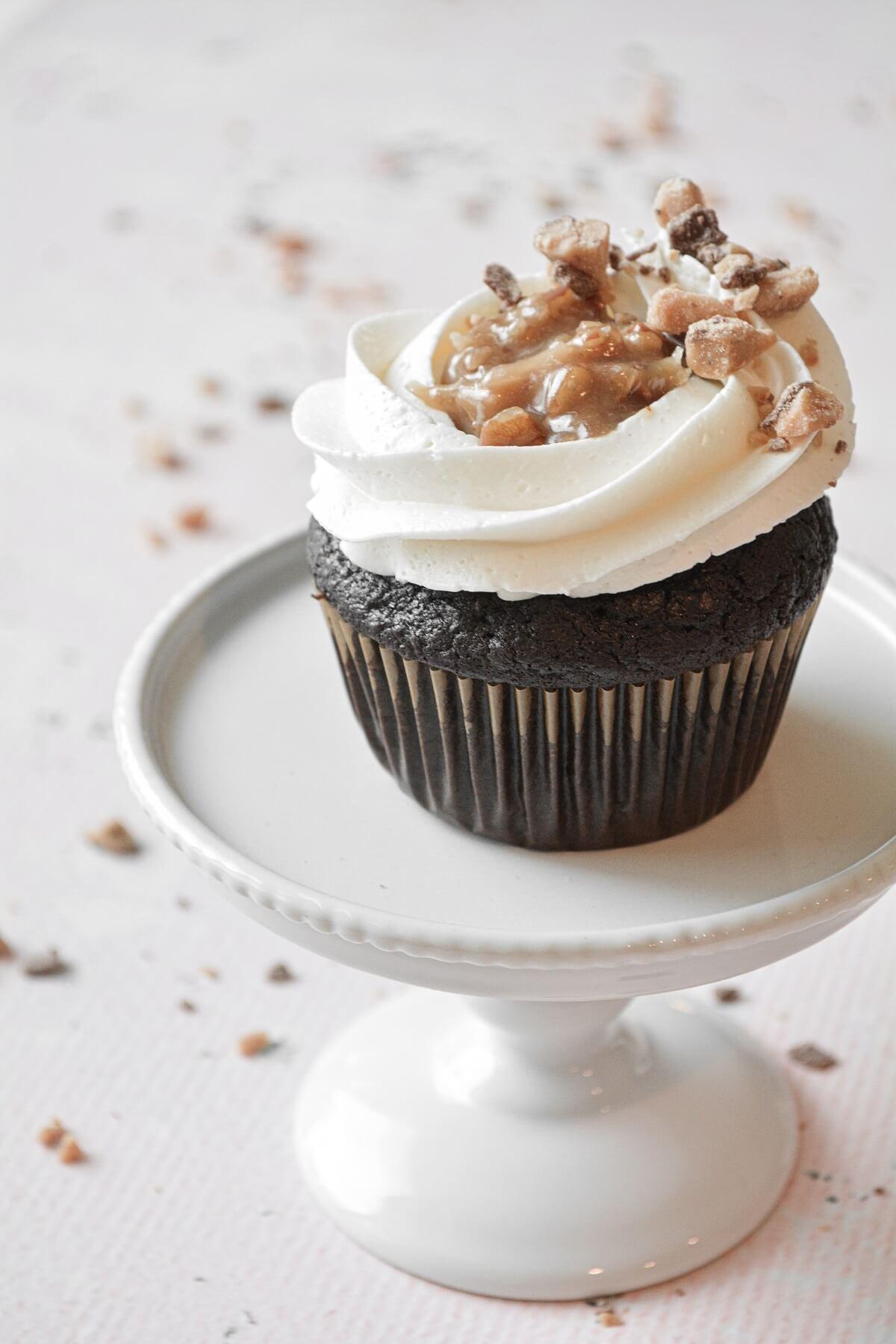A German chocolate bourbon cupcake with vanilla buttercream and pecan, coconut caramel filling.