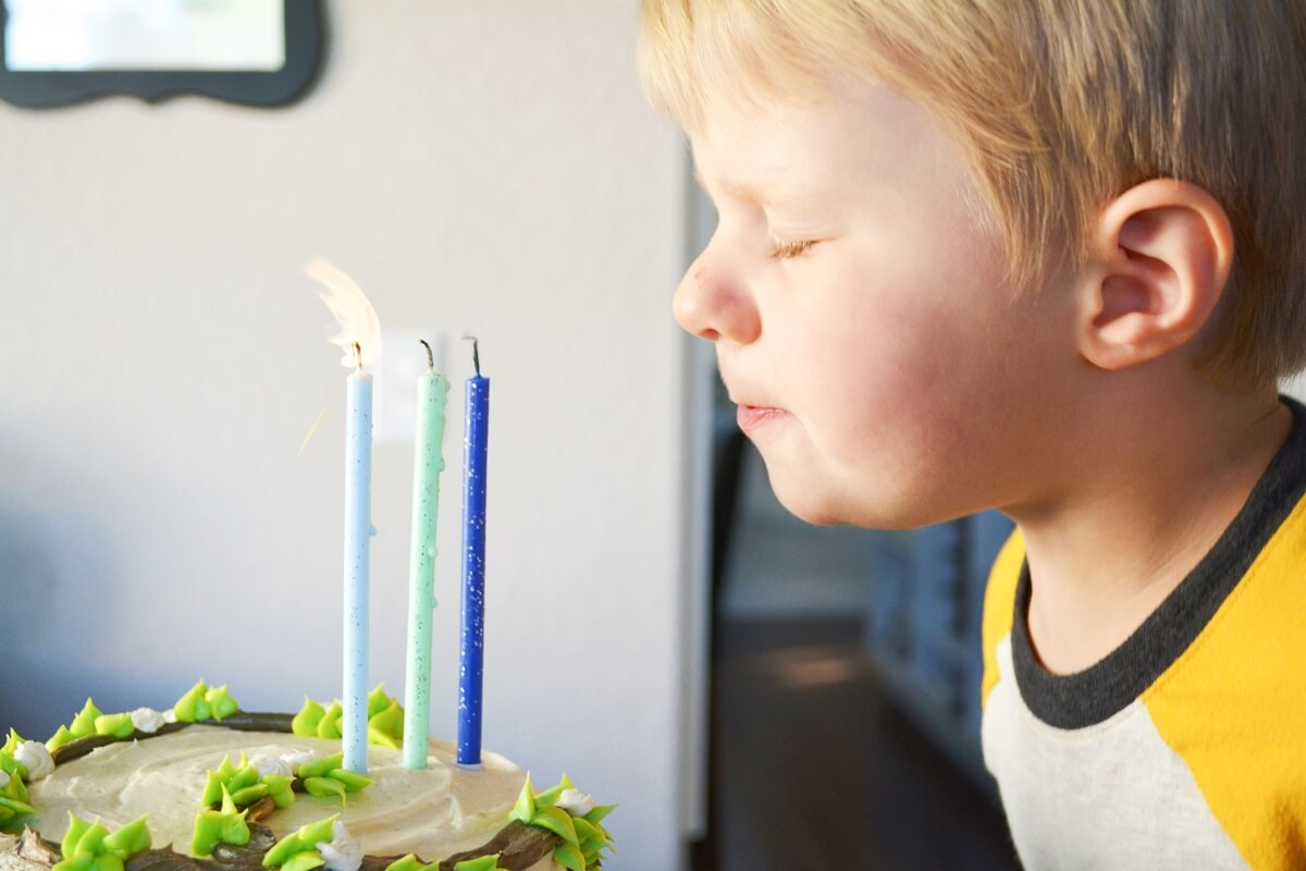 A little boy, blowing out three birthday candles on a Goldie and Bear cake.