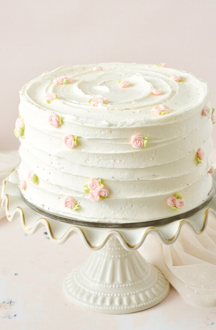 Lemon cake decorated with pink buttercream rosettes.