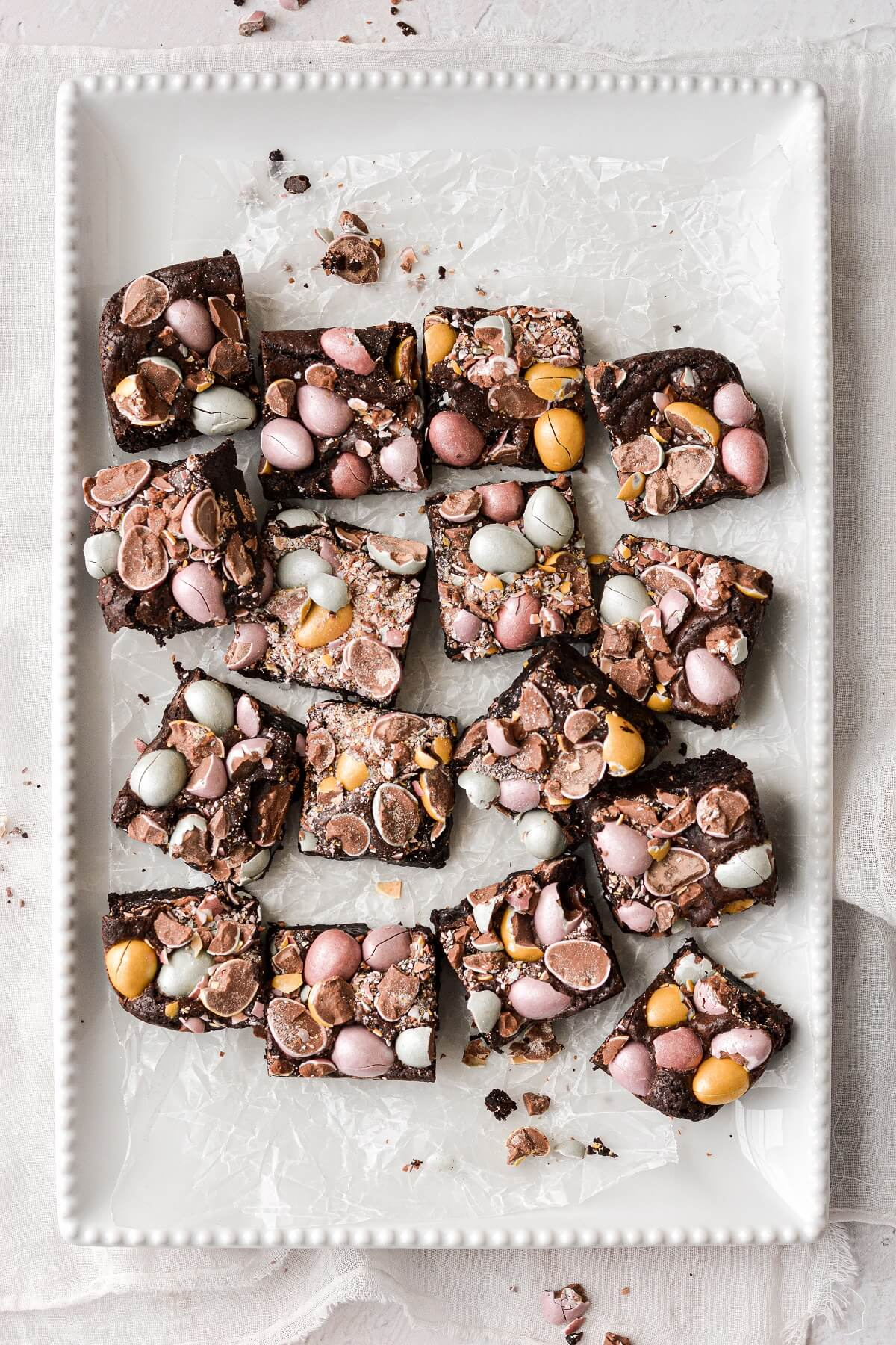 Mini cadbury egg Easter brownies, cut into squares on a white platter.