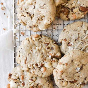 Nutty chocolate chip cookies, with white chocolate and butterscotch chips, arranged on a cooling rack.