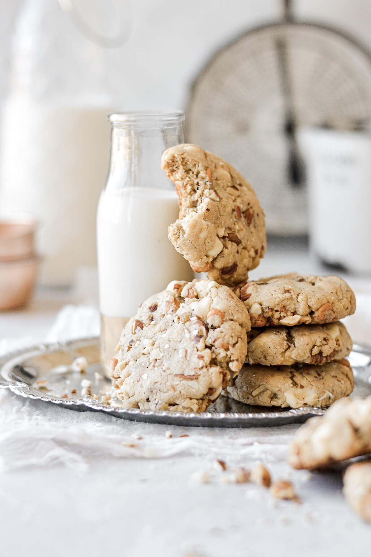 A stack of nutty chocolate chip cookies, one with a bite taken, next to a jar of milk.