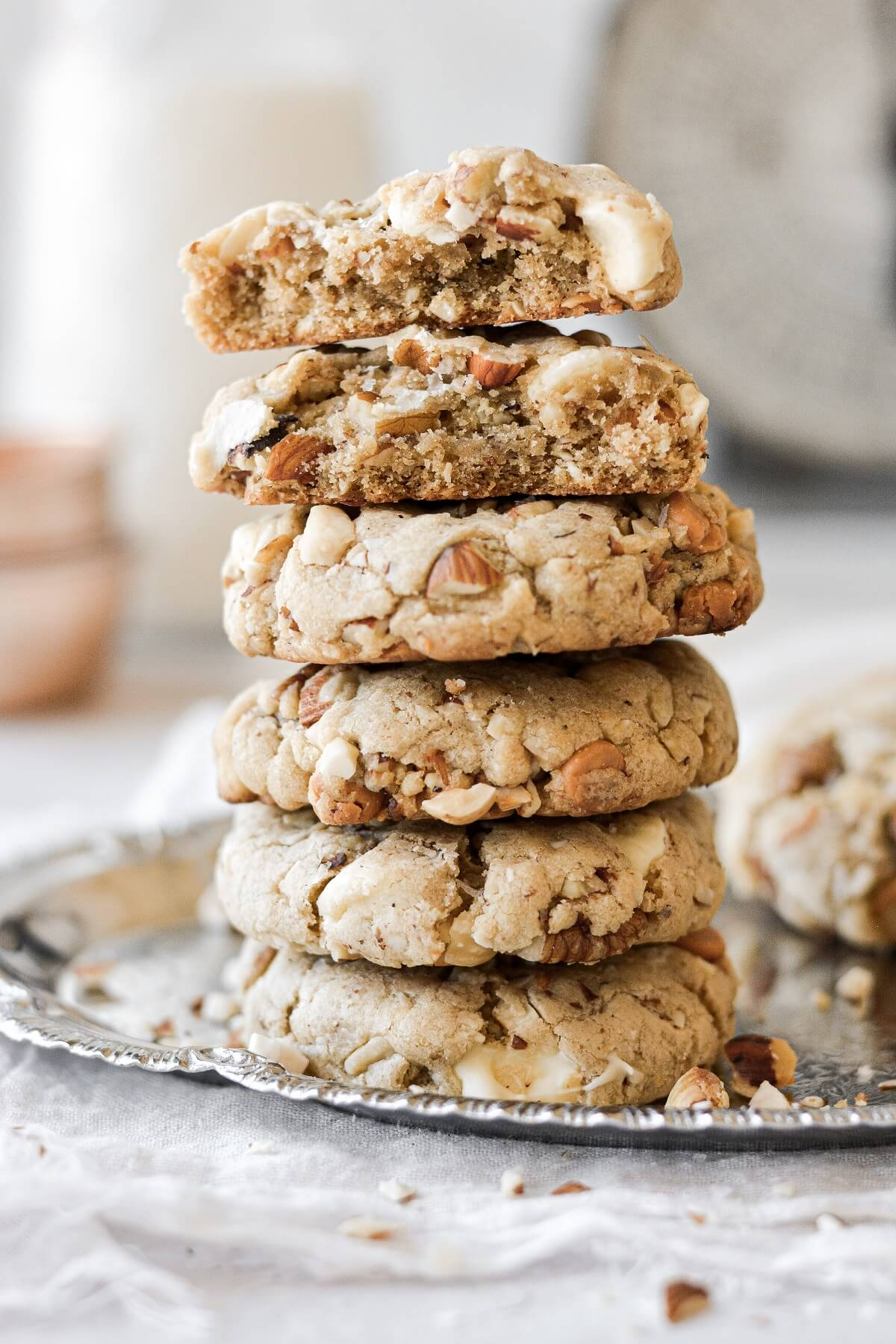 A stack of nutty chocolate chip cookies, one broken in half.