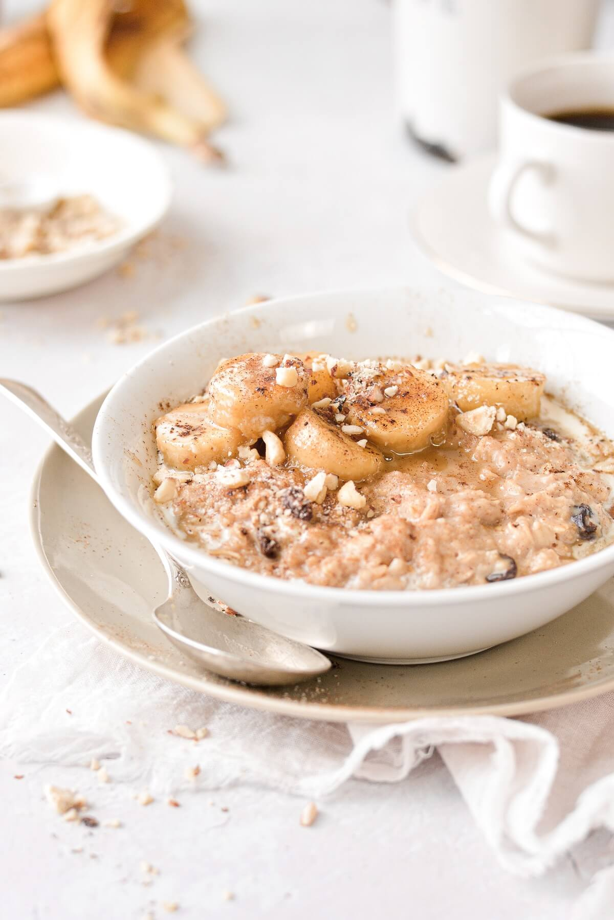 A bowl of oatmeal topped with caramelized bourbon bananas and chopped hazelnuts.
