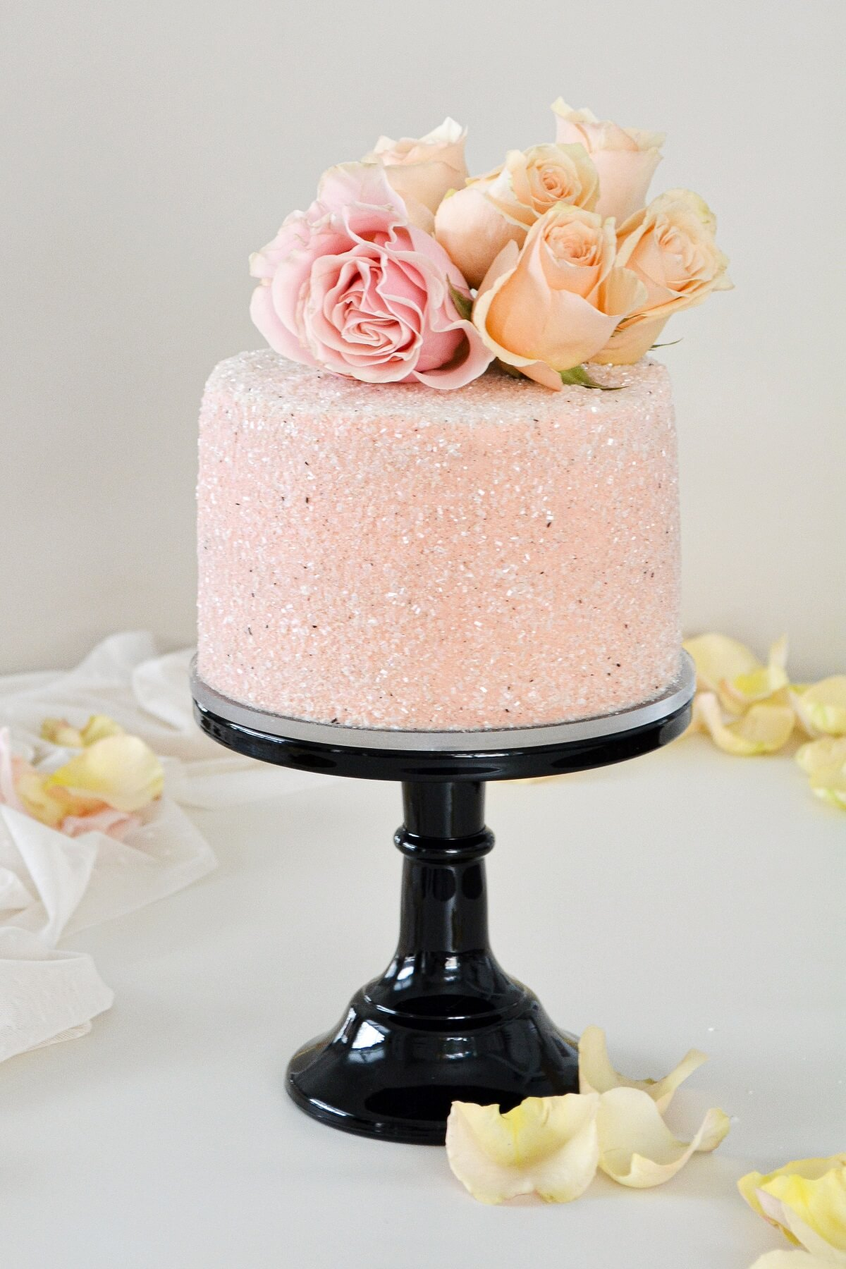 Chocolate peppermint cake, covered in pink sparkling sugar and pink and peach roses.