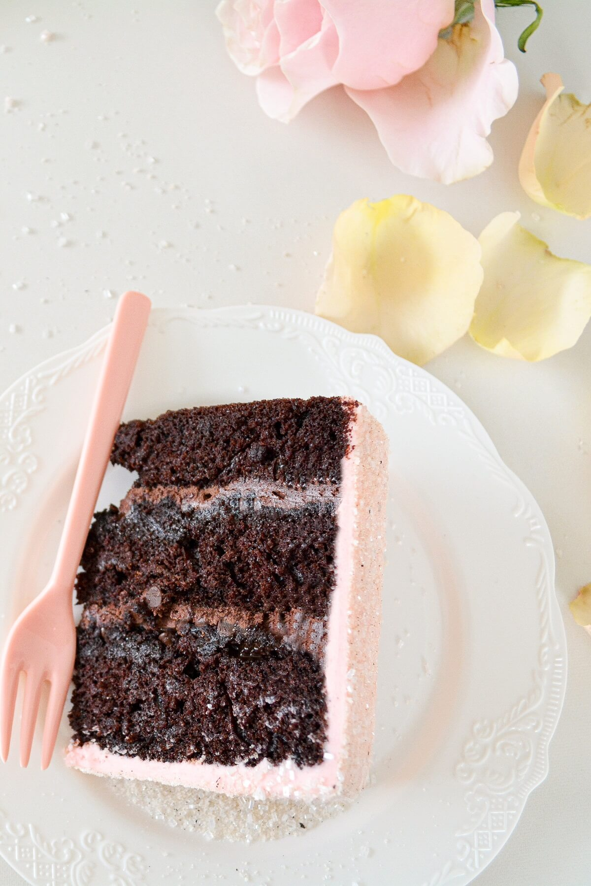 A slice of chocolate cake with chocolate filling and pink peppermint buttercream.