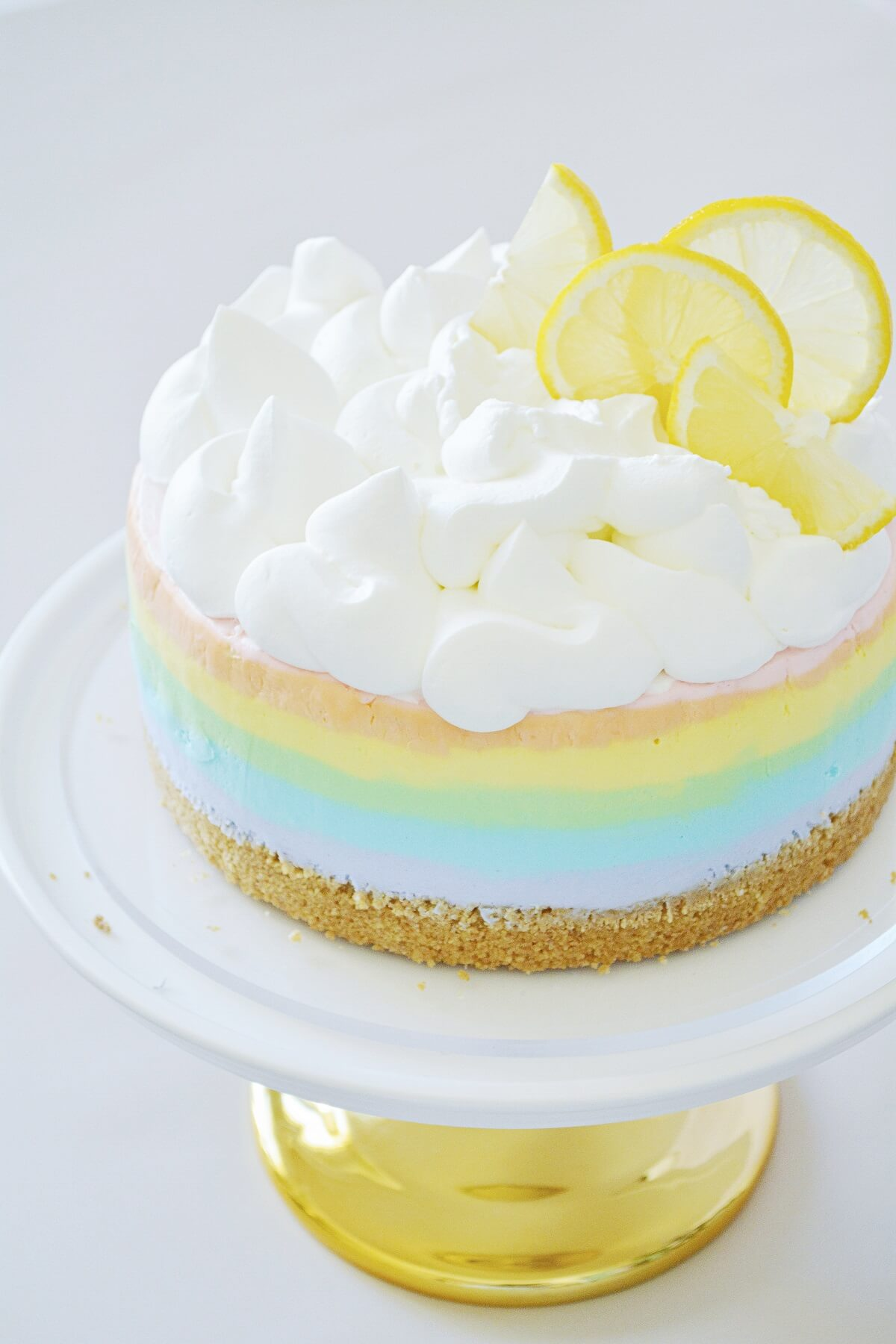 Rainbow cheesecake, topped with whipped cream and lemon slices.