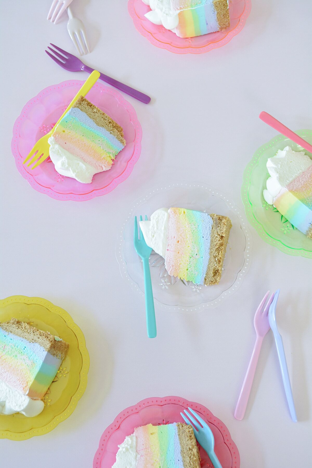 Slices of rainbow cheesecake on colorful plates.