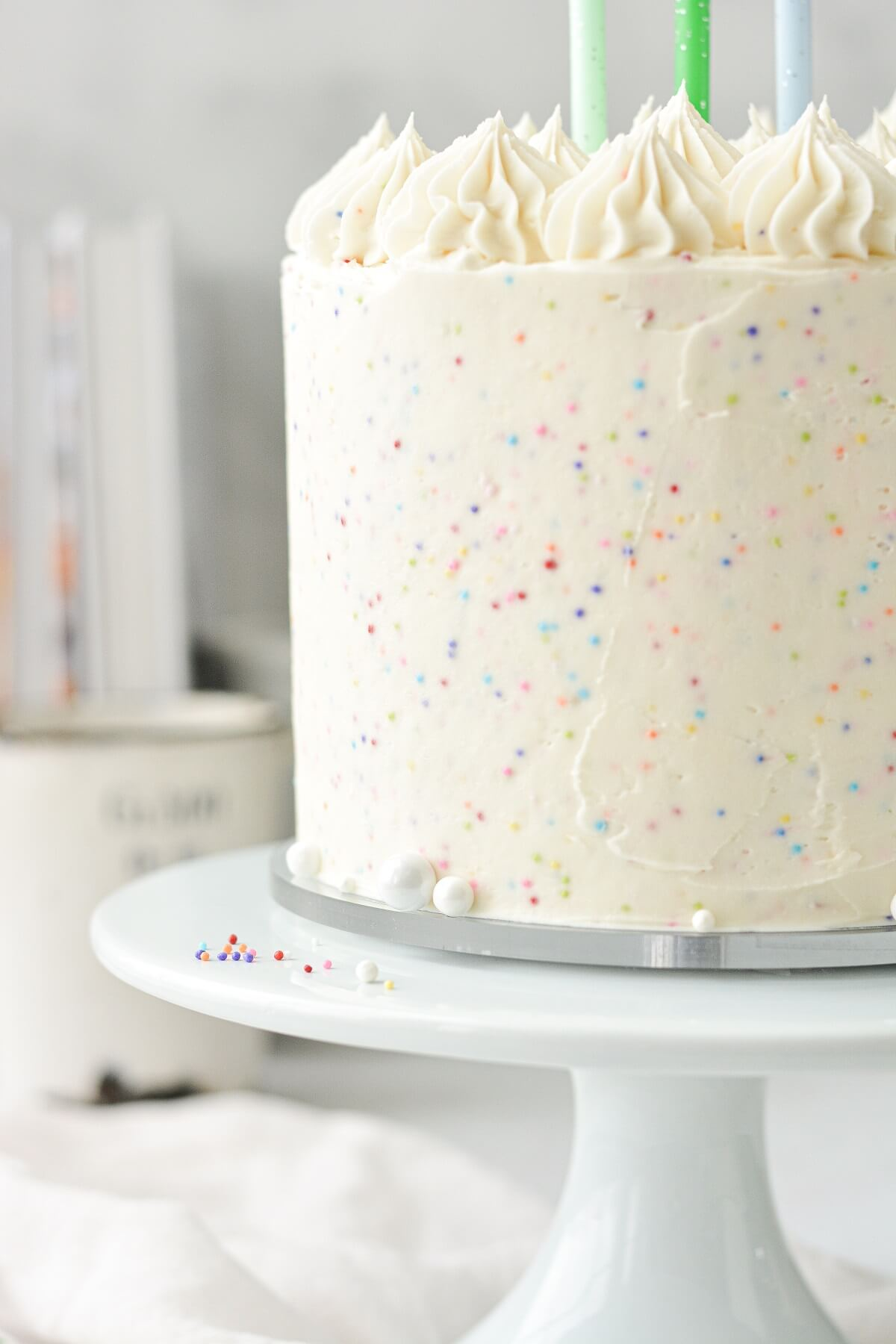 Rainbow cake frosted with sprinkle buttercream and topped with three birthday candles.