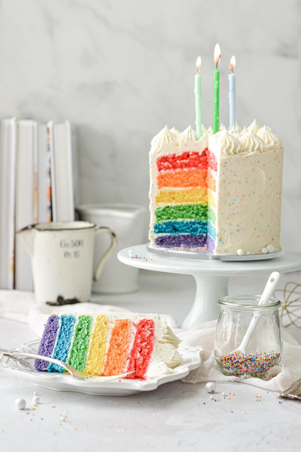 Rainbow cake topped with three birthday candles, with one piece cut.