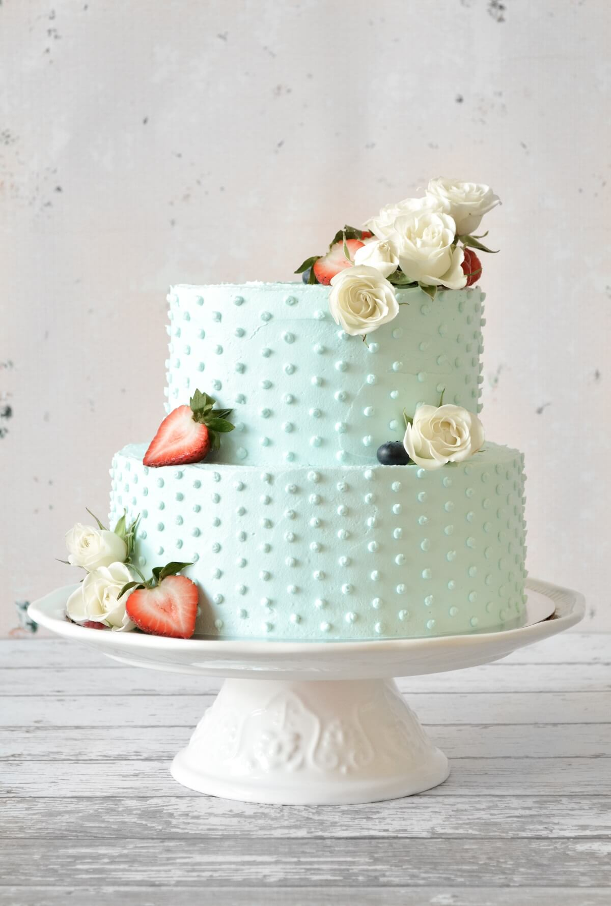 A red, white and blue, two-tiered cake with blue buttercream, swiss dots, strawberries and white roses.