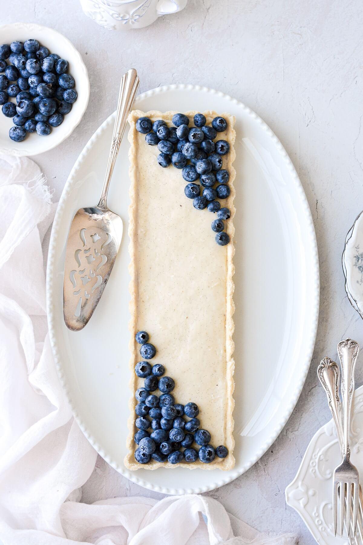 A long vanilla bean custard tart on an oval platter, topped with blueberries.