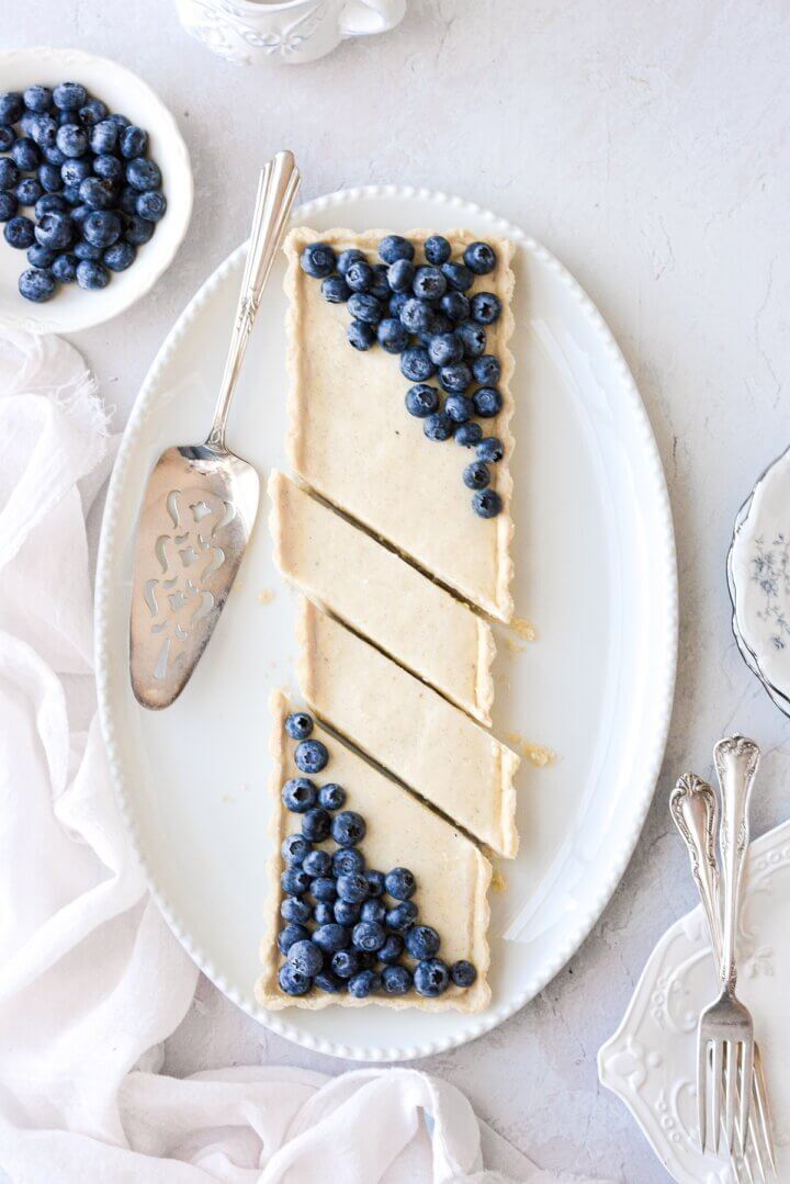 A long vanilla bean custard tart on an oval platter, topped with blueberries and cut into diagonal slices.