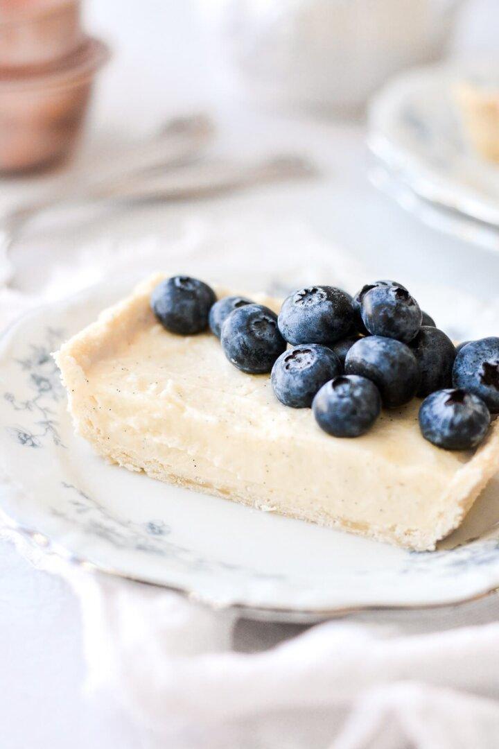 A slice of vanilla bean custard tart topped with blueberries.
