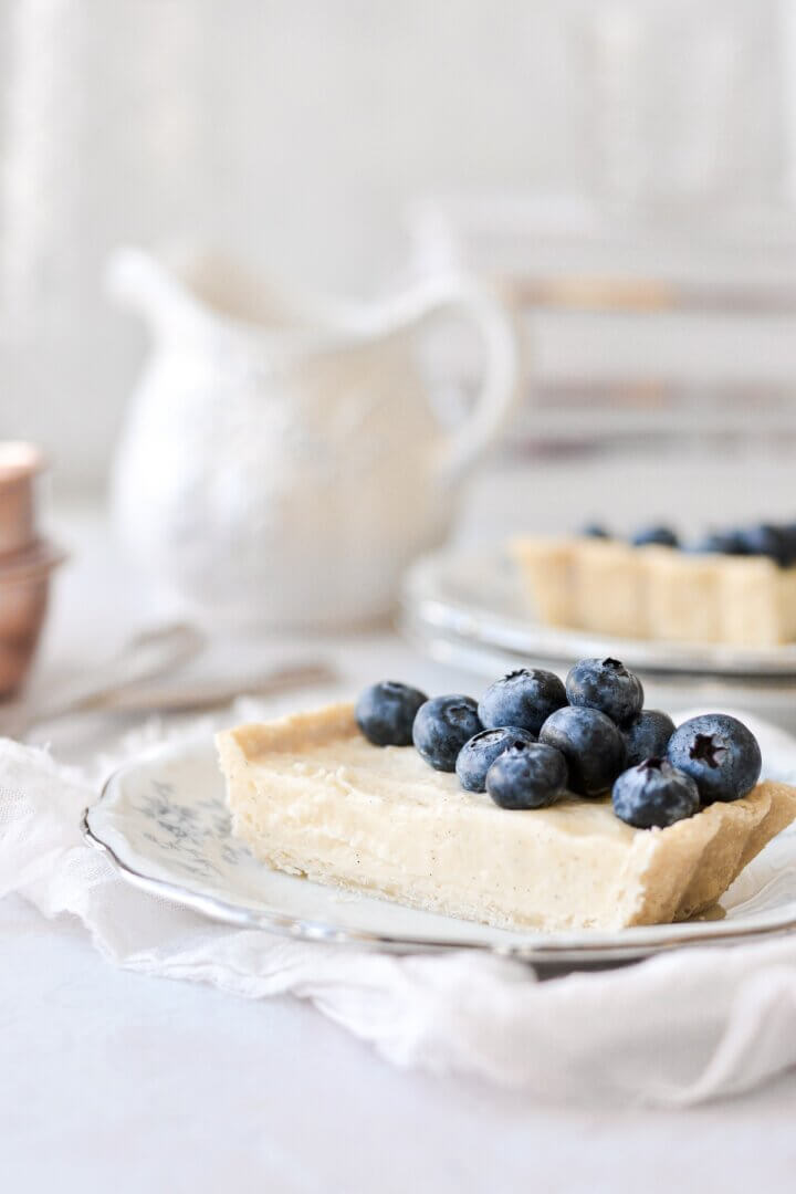 A slice of vanilla bean custard tart topped with blueberries.