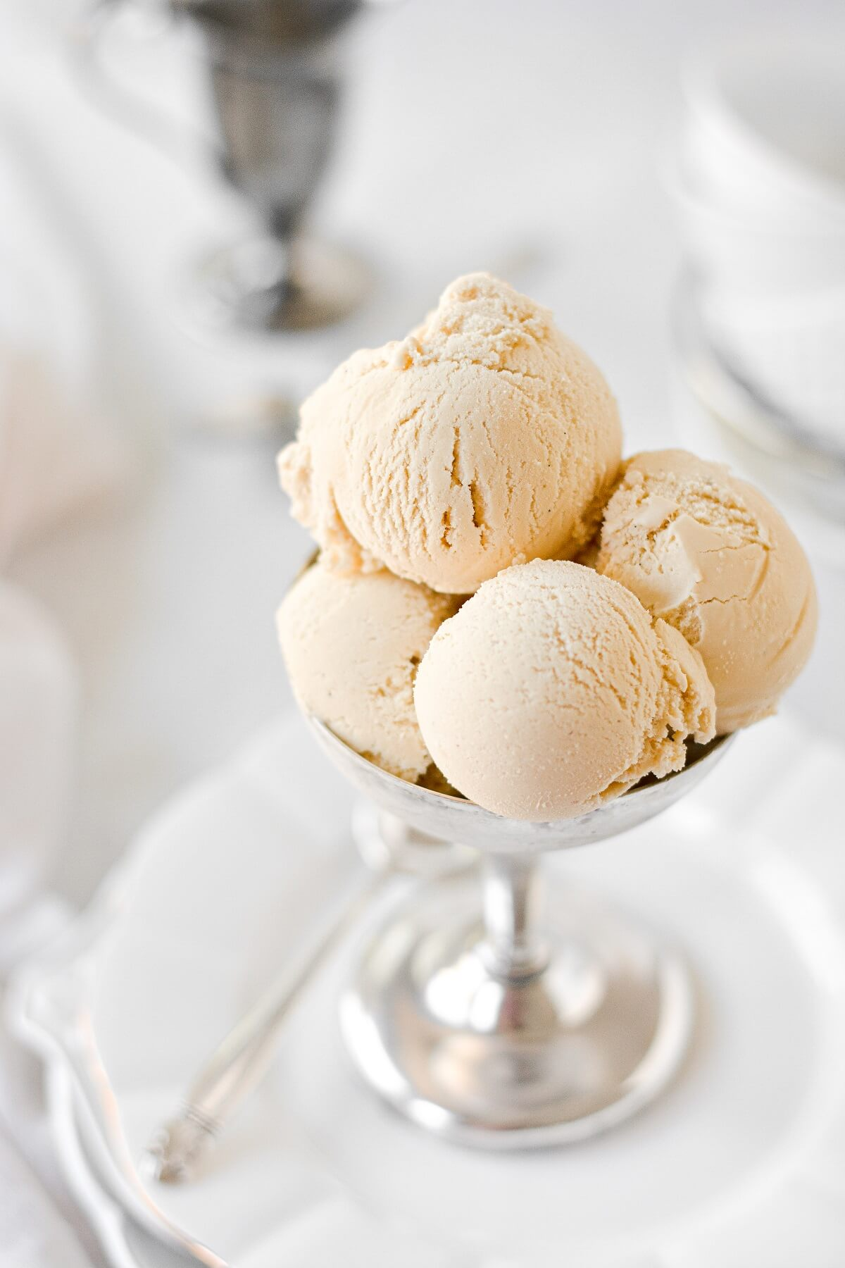 Scoops of brown sugar ice cream in a silver footed bowl.