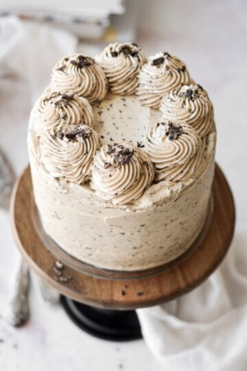 Chocolate peanut butter cake topped with swirls of frosting and chopped chocolate.