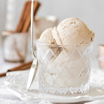 Cinnamon ice cream in a glass, with a spoon resting against the glass.