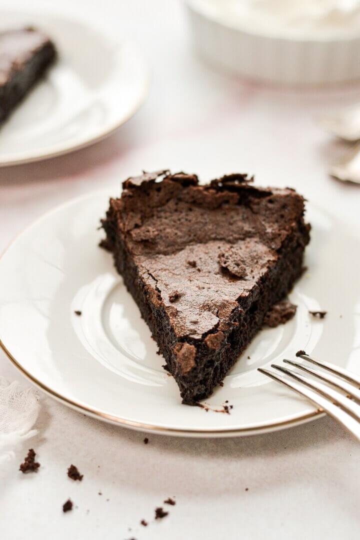A slice of flourless chocolate cake on a white plate.